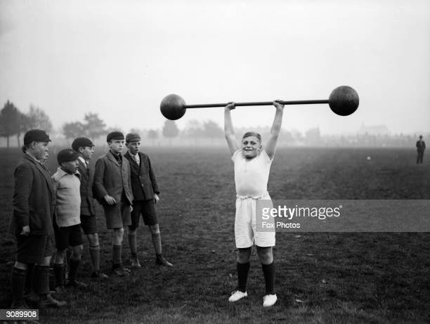 Northampton schoolboy William Albert Tuckley raises a dumbbell weighing 110 pounds above his head to the amazement of his classmates Elevenyearold...
