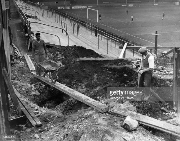 players train on the pitch as builders get to work on the new stand at Brentford Football Club's Griffin Park stadium in West London