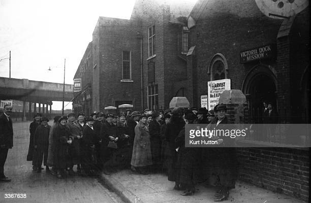 A group of elderly women queuing outside Victoria's Dock Mission East London to join the weekly meeting of their 'Grandmother's Club' Original...