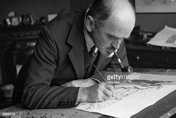 British political cartoonist David Low at work in his studio in London drawing a cartoon for the 'Evening Standard' newspaper Original Publication...