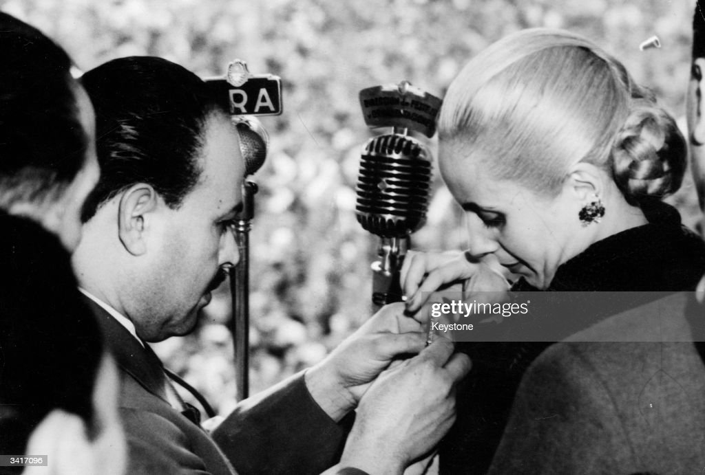 Eva Peron (1919 - 1952), wife of the Argentine President receives a decoration from Mr Espejo, Chief of the CGT worker's organisation at a 'Loyalty Day' ceremony in Buenos Aires. It is her first appearance after a serious illness.