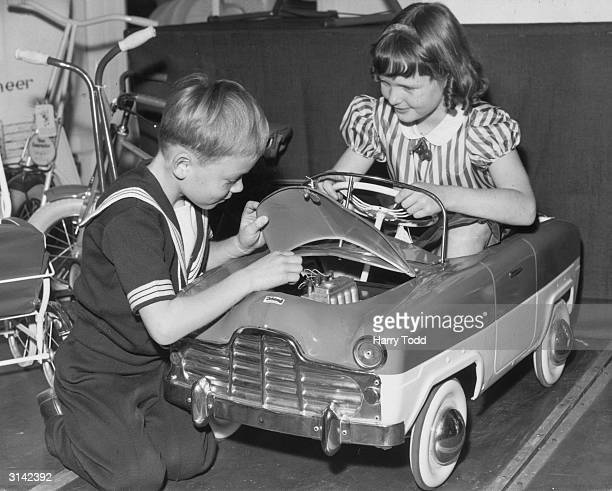 Six year old David Burt takes a look under the bonnet while his nine year old sister Susan sits at the wheel of a toy car at a toy display at the...