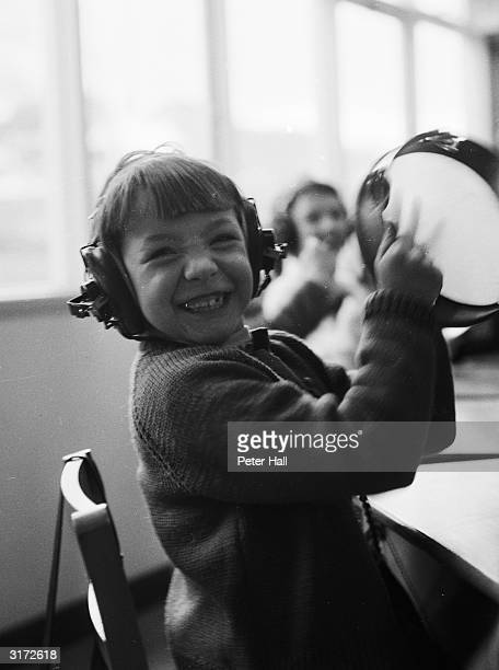 During a music lesson at the Ewing school for deaf children in Nottingham a boy clearly enjoys using his tambourine to add sounds to recorded music...
