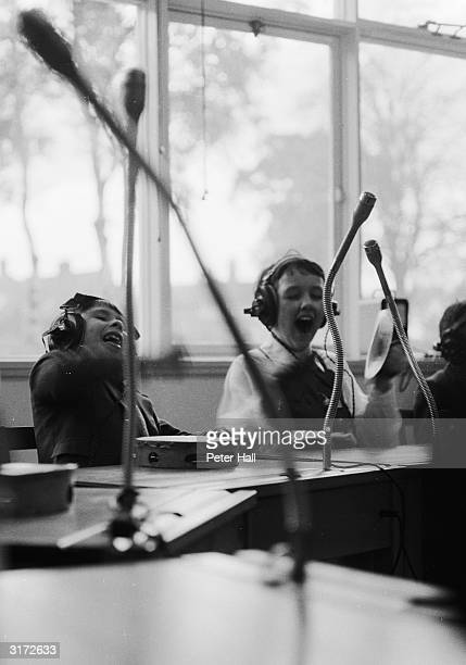 During a music lesson at the Ewing school for deaf children in Nottingham two boys use tambourines to add sounds to recorded music which they can...