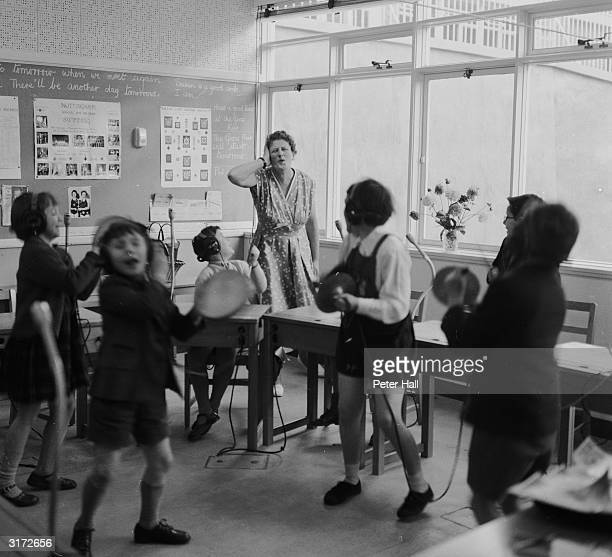 Teacher Dorothy Marriot gives a music lesson at the Ewing school for deaf children in Nottingham The children are using cymbals and tambourines to...