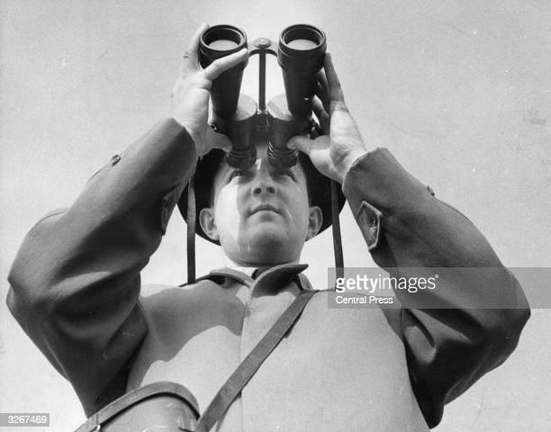 A man uses large highpowered binoculars to follow a horserace
