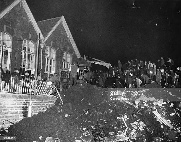 A mechanical digger goes to work clearing rubble from the crushed village school at Aberfan South Wales which was engulfed after a coal tip collapsed...