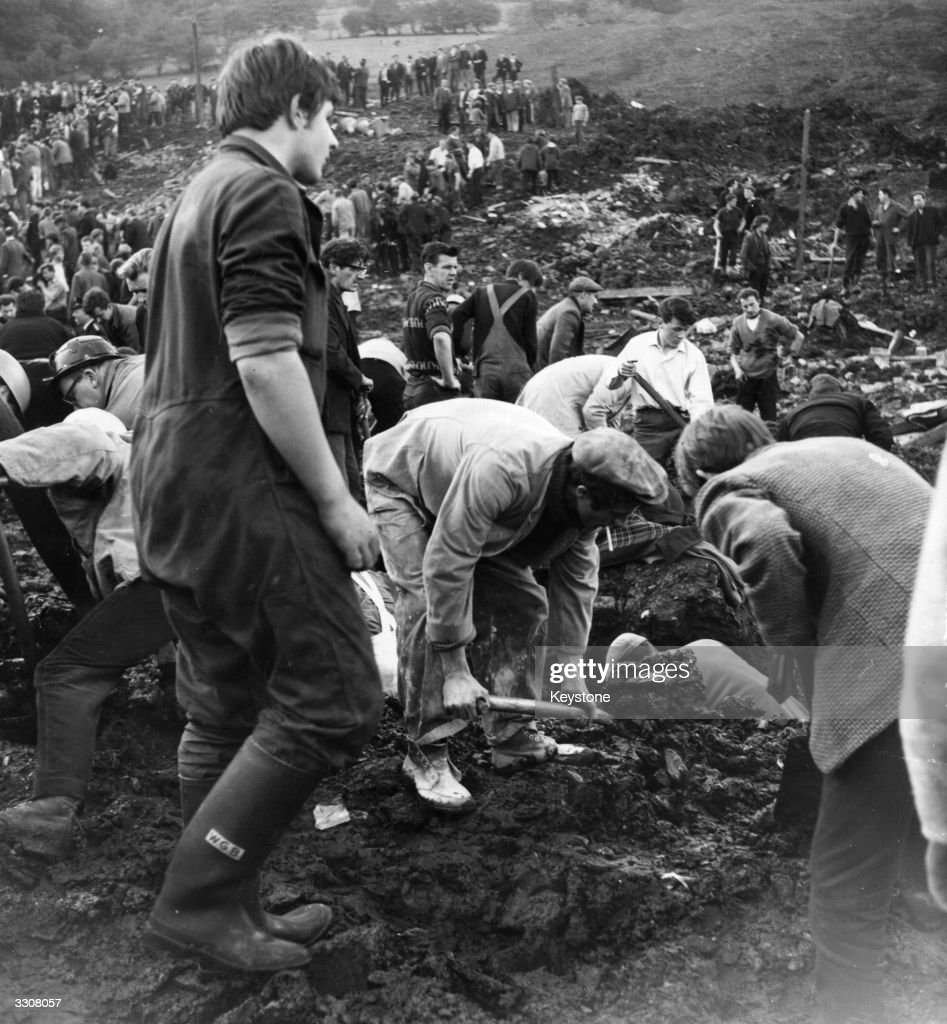 Rescue workers clearing debris and sludge near the wrecked Pantglas Junior School at Aberfan, South Wales, where a coal tip collapsed killing many children.