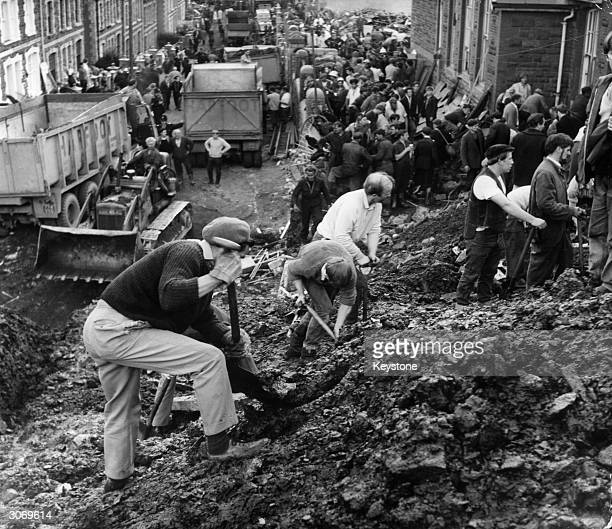 Rescue workers digging amongst the rubble and mud at Aberfan when a rainsoaked coal tip engulfed an infant's school houses and a farm 144 people were...