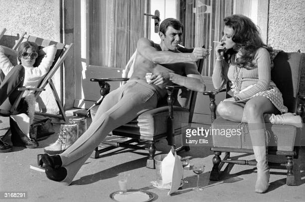 Stripped to the waist Australian actor George Lazenby offers costar Helena Ronee a light whilst filming the new James Bond film 'On Her Majesty's...