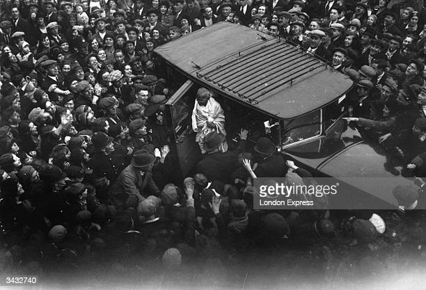 An admiring East End crowd gathers to witness the arrival of Mahatma Gandhi in Canning Town East London as he calls upon Charlie Chaplin Gandhi is in...