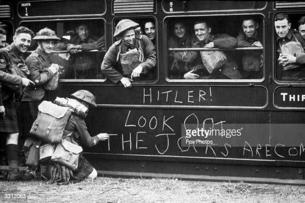 A soldier of the Cameron Highlanders chalks a warning to Hitler on the side of a train as troops leave Aldershot for France It reads 'Hitler Look oot...