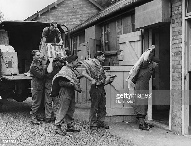 British soldiers carrying rations into some converted stables at a racecourse which is serving as an army base