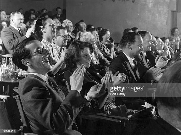 Members of an audience at the Players' Theatre at Hungerford Arches, London, watching a production based on the Victorian Music Hall. Original...