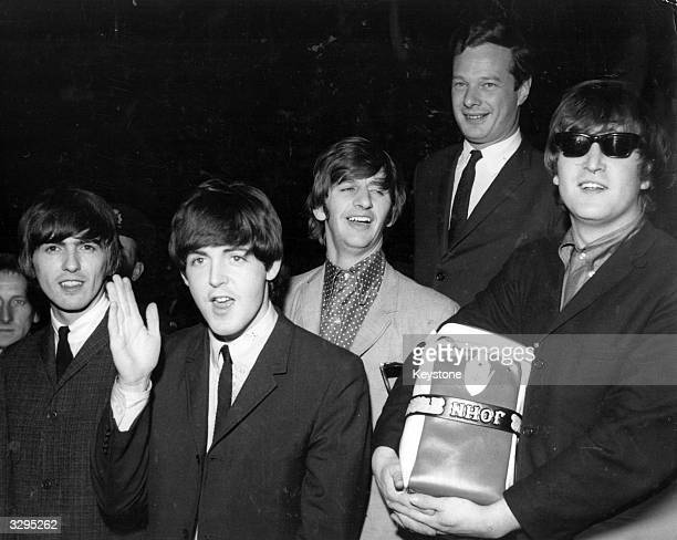 The Beatles from left to right George Harrison Paul McCartney Ringo Starr manager Brian Epstein and John Lennon at London Airport They arrived to a...