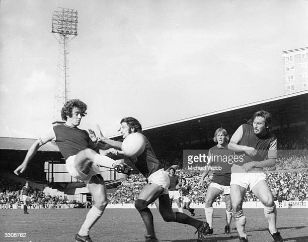 Ted McDougall of West Ham United and Frank Worthington of Leicester City contend for the ball as West Ham's Tommy Taylor and Billy Bonds look on...
