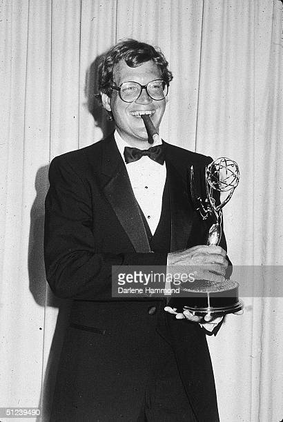 22nd September 1985 American comedian and talk show host David Letterman smokes a cigar and smiles while holding his trophy for Outstanding Writing...