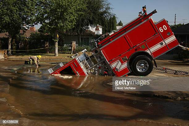 A 22ton Los Angeles Fire Department fire truck protrudes from a sinkhole on September 8 2009 in the Valley Village neighborhood of Los Angeles...