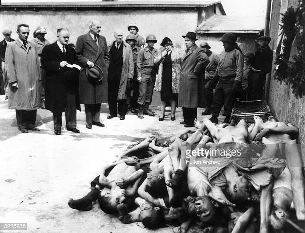 Fulllength view of British MPs a journalist and soldiers standing behind a heap of emaciated naked corpses at the concentration camp in Buchenwald...