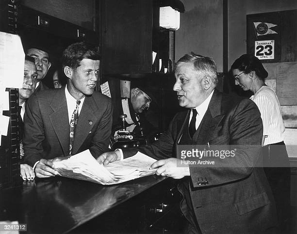 American politician John Fitzgerald Kennedy files his first nomination papers with election commissioner Joseph Langone at City Hall Boston...