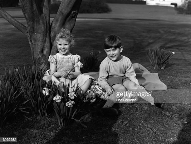 Princess Anne and Prince Charles sitting on a picnic rug in the grounds of the Royal Lodge at Windsor