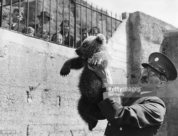 Threemonth old Nikki a Russian bear cub a gift to Princess Anne from the Russian leaders being held up by his keeper at the London Zoo