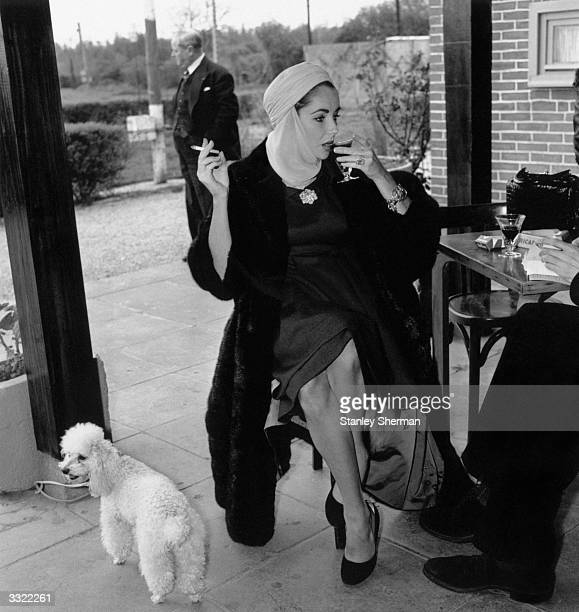 American actress Elizabeth Taylor sips a drink and smokes a cigarette during a stop for interviews at Jersey airport en route to Nice