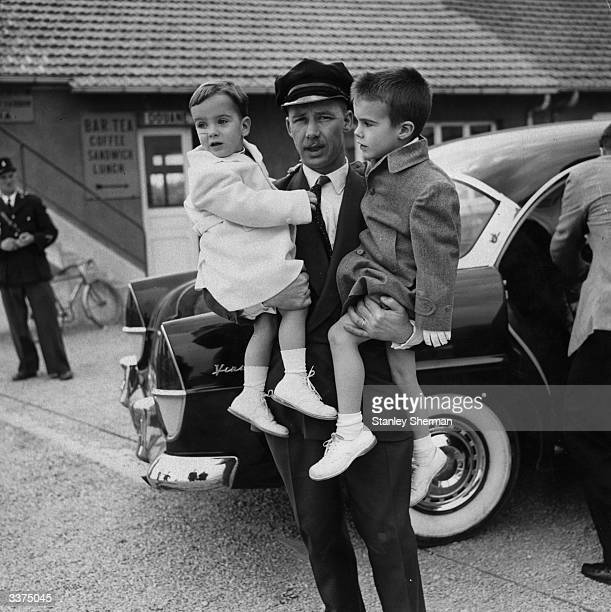 Elizabeth Taylor's children Christopher left and Michael Wilding Jnr being carried from the car by a chauffeur during a stopover at Jersey en route...