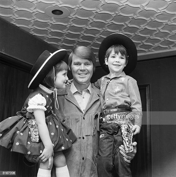 American country singer and actor Glenn Campbell was presented with a birthday cake by 4 year old Renata Ronol and 6 year old cowboy, Francis...
