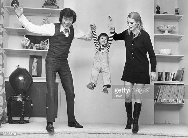 Dancer Lionel Blair and his wife Susan swinging their son David between them