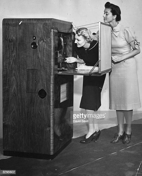 Two women at the Television and Radio Show at Olympia Exhibition Centre London take a close look at the new television set which retailing at 231 is...