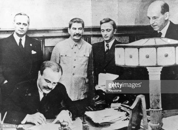Vyacheslav Molotov Russian Foreign Minister signs the nonaggression pact negotiated between Soviet Russia and Germany at the Kremlin Moscow Standing...