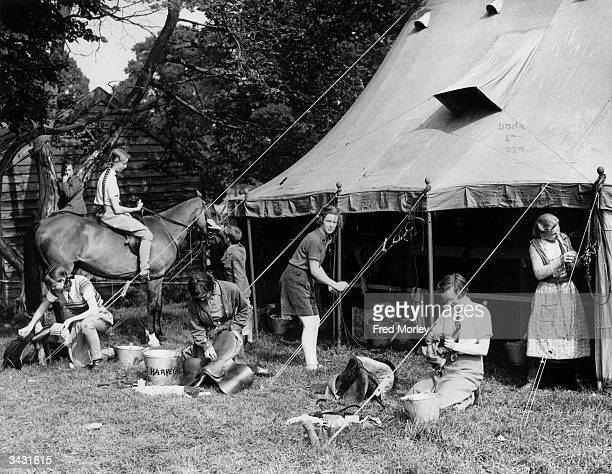 Young members of the Oakley Hunt Pony Club polishing their saddles and bridles at the summer camp in Evershot Bedfordshire where they are receiving...