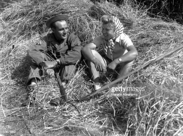 An American soldier and a land girl take a rest from pitching wheat in the farmyard Many American soldiers have volunteered to help gather the...