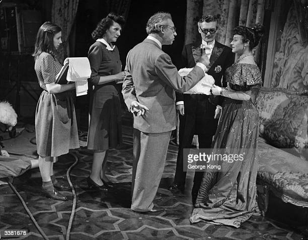 Script girls stand by as Hungarianborn British film director and producer Alexander Korda explains the next sequence to Paulette Goddard and Hugh...