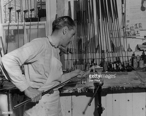 A workman fitting a shaft to a golf club head in the workshop of Tom Morris in St Andrews Scotland