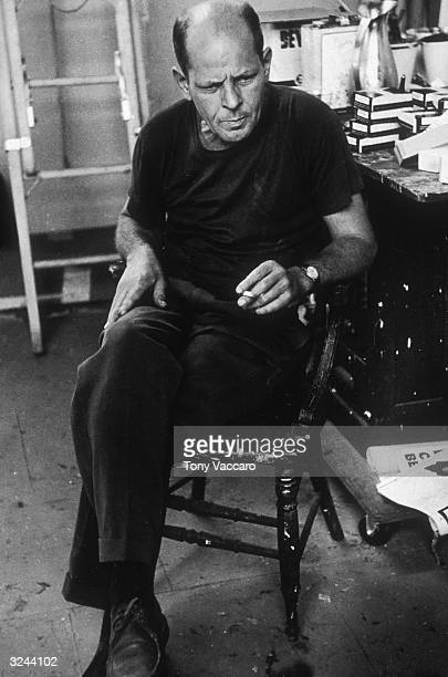 American painter Jackson Pollock sits in his studio known as 'The Springs' holding a cigarette with his legs crossed East Hampton New York