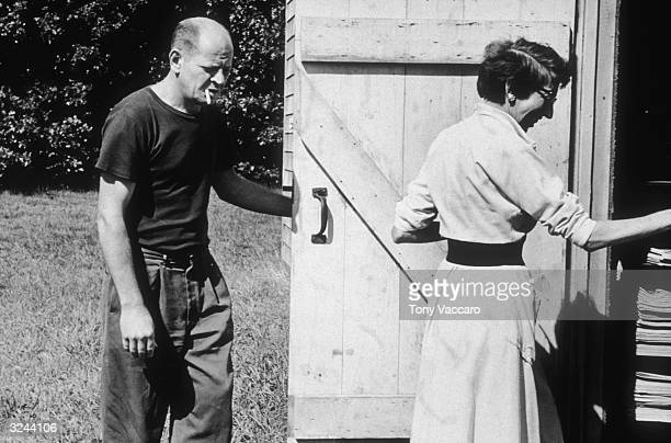 Married American painters Jackson Pollock and Lee Krasner enter the barn door of their studio 'The Springs' in East Hampton New York