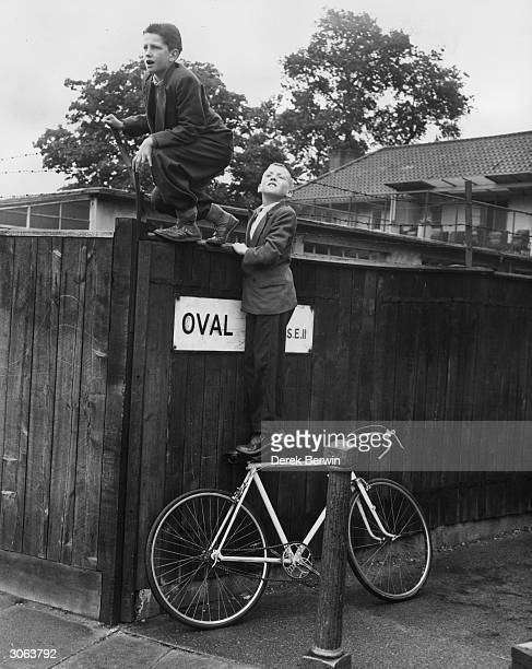 Fred Titchener and his friend Arthur Maret peer over the fence at the Oval cricket ground in south London during the final Test Match of the 1956...