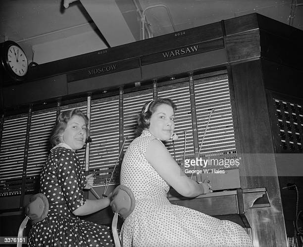 Twins Valerie and Christine Harris operate the General Post Office's long distance telephone switchboard to Moscow and Warsaw from the GPO...