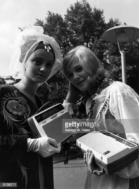 Air hostesses Suna Palamutcuogollari from Turkey and on the right Kirsten Krogirus from Finland listen to a transistor radio while they wait for the...