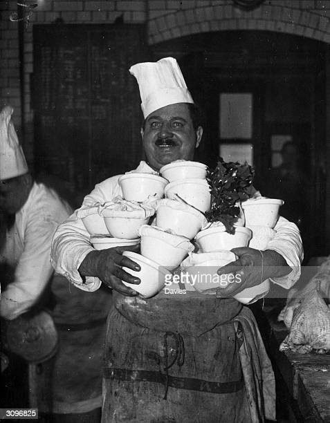 A chef carrying an armful of Christmas puddings to feed the passengers travelling on an LMS train from Euston Station London during the Christmas...