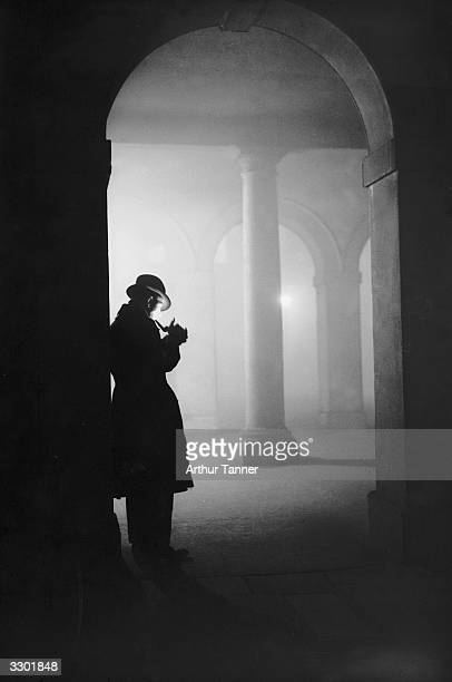 A man lighting his pipe in thick fog under the arches at the Temple London