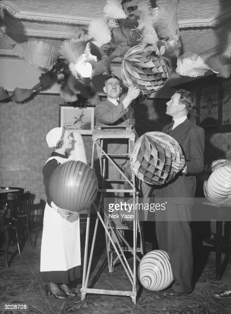 Bradshaw and Hobson of Liverpool FC putting up decorations for a Christmas party at a hotel in Rhyl where the club is about to begin training for...