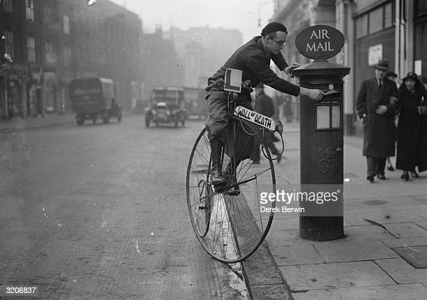 Mr Tornado Smith posts a letter while riding penny farthing bicycle He is wearing a learner plate and his bike is advertising his Wall of Death act