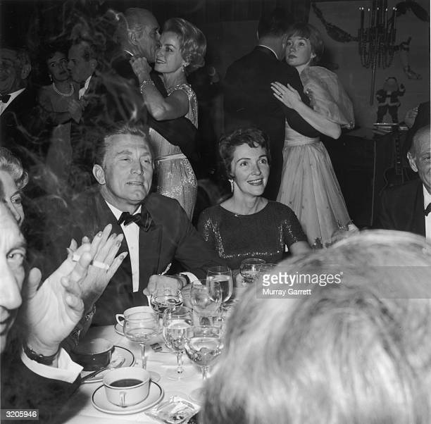 EXCLUSIVE American actors Kirk Douglas and Nancy Reagan sit at a dinner table as actor Shirley MacLaine dances with an unidentified man behind Reagan...