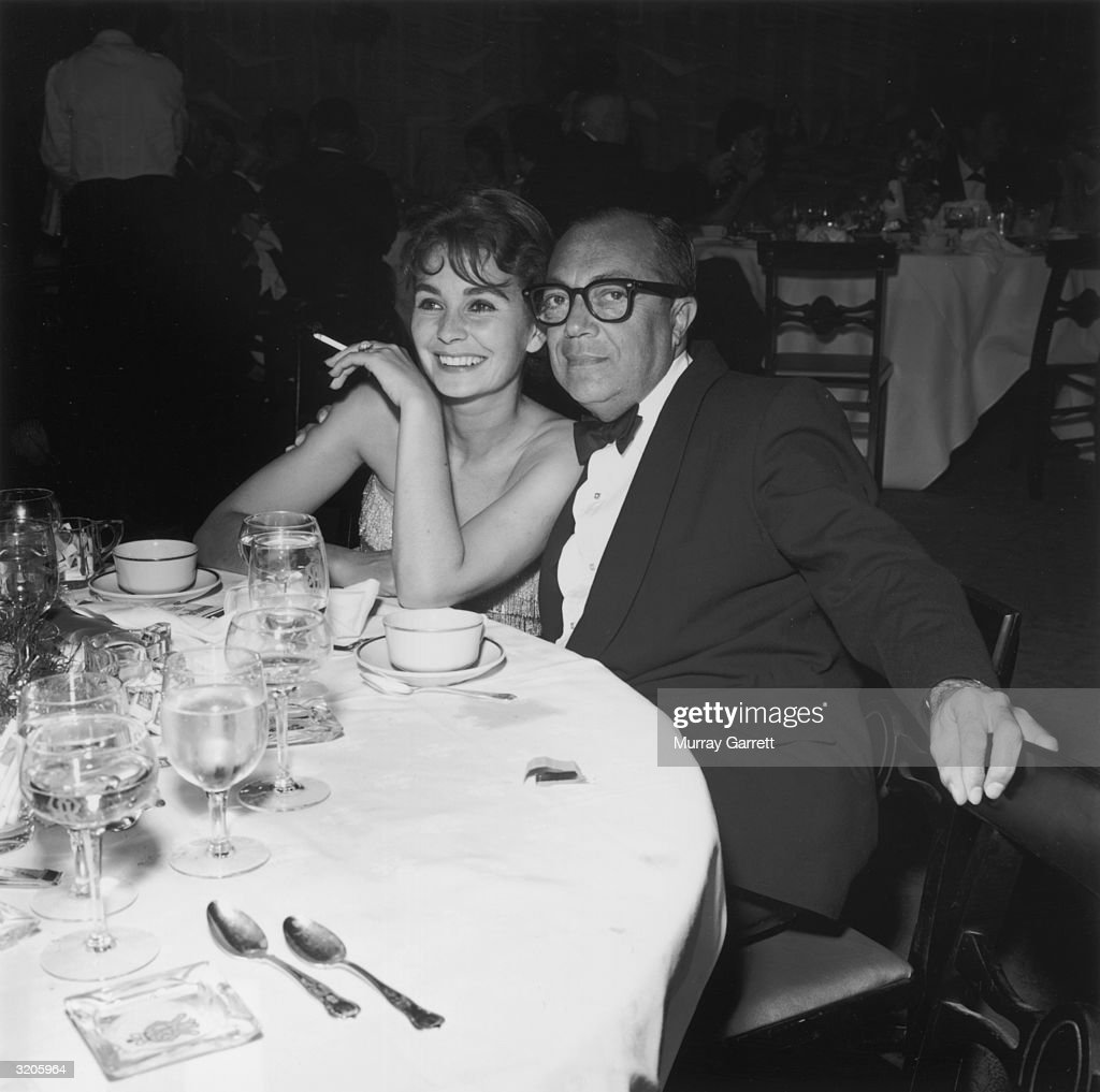 British-born actor Jean Simmons smiles while sitting with American film producer Harold Mirisch at a table for a Thalians party, Hollywood, California. She holds a cigarette.