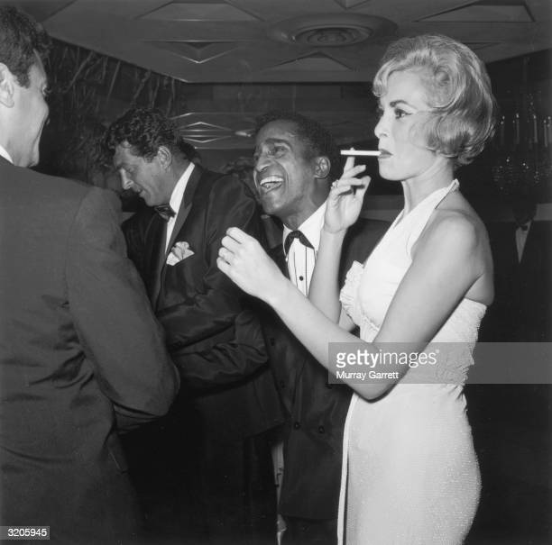 American actor Tony Curtis speaks with entertainers Dean Martin and Sammy Davis Jr. , as Curtis' wife, Janet Leigh, smokes a cigarette, at a Thalians...