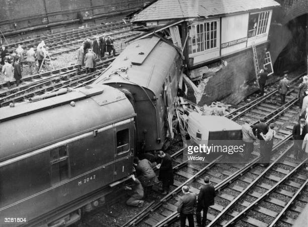 People on the tracks after a crash in which a sleeping car smashed into the signal box at Islip Street Junction north London