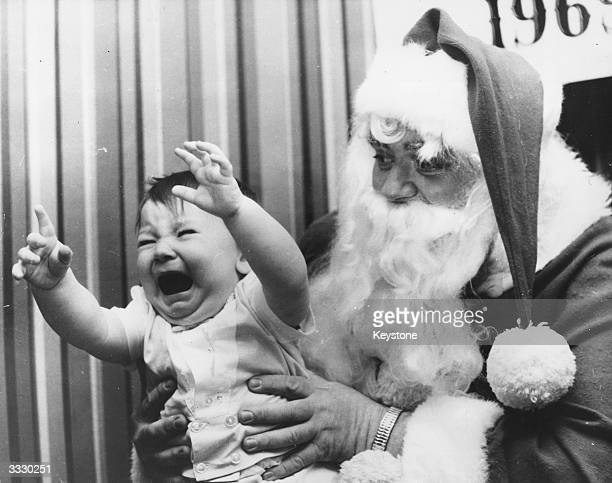 A baby screams in the arms of a traditional English Santa Claus